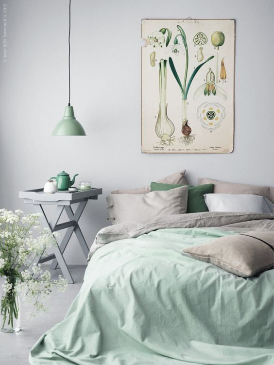 a subtle spring bedroom with grey and green bedding, a vintage botanical poster and a green lamp is a tender space