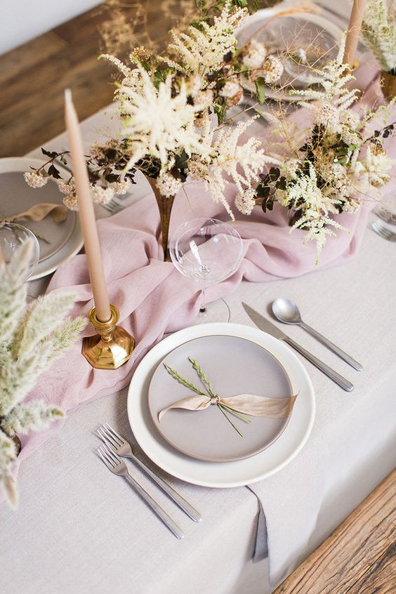 a tender spring tablescape done in the shades of pink, with matte porcelain, blush candles and spring blooms in vases