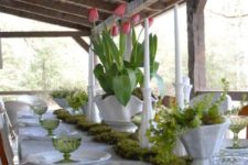 a thrifted spring table setting with pink tulips, grene glasses, a moss runner and a greenery centerpiece