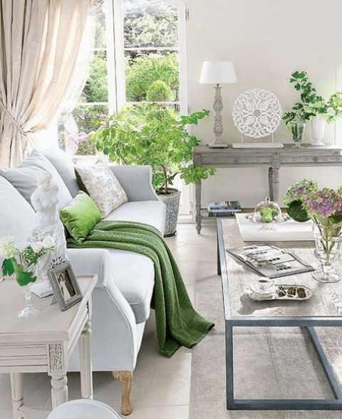 a vintage farmhouse living room with pastel and wooden furniture, potted greenery and blooms and refined art
