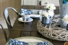 a vintage-inspired sprign table setting with navy printed napkins, a white and blue floral centerpiece and printed porcelain