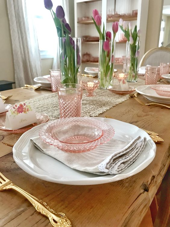 a vintage-inspired spring tablescape with pink glass, pink tulips in vases and a lace table runner