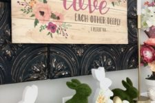 a whimsy Easter mantel with a large floral sign, some bunnies – of moss and with floral prints and some faux eggs