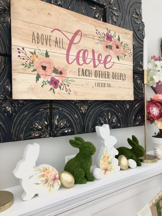 a whimsy Easter mantel with a large floral sign, some bunnies - of moss and with floral prints and some faux eggs