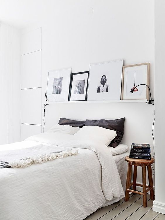 a white Nordic bedroom with a ledge with artworks, a comfy bed, wooden stools as nightstands and lamps