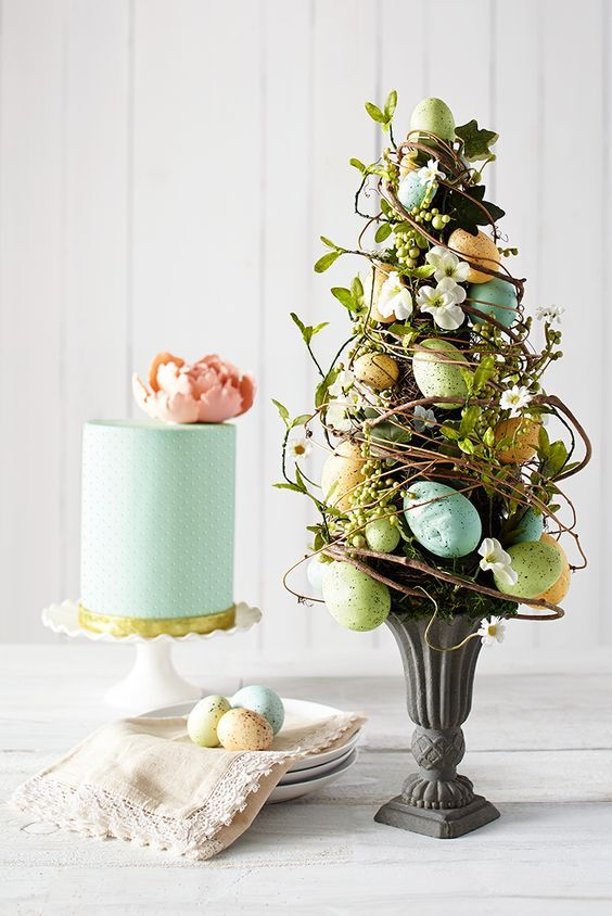 an Easter flower arrangement designed as a tree   with vines, greenery, blooms and pastel eggs