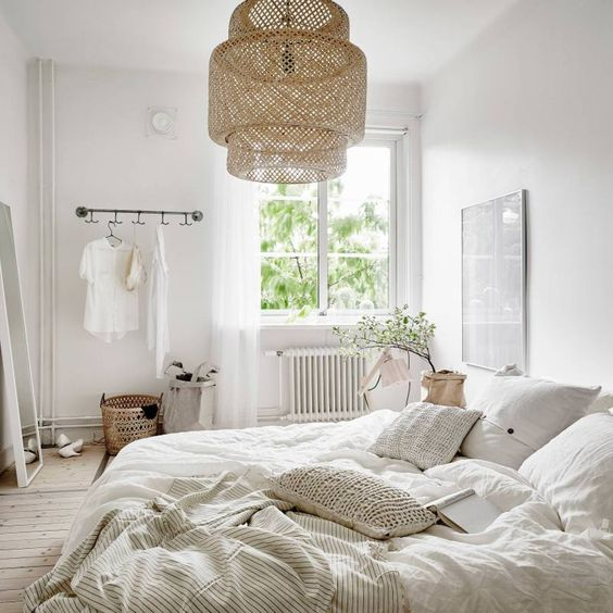 an airy Nordic bedroom with a wicker lampshade, crochet pillows, neutral furniture and much light