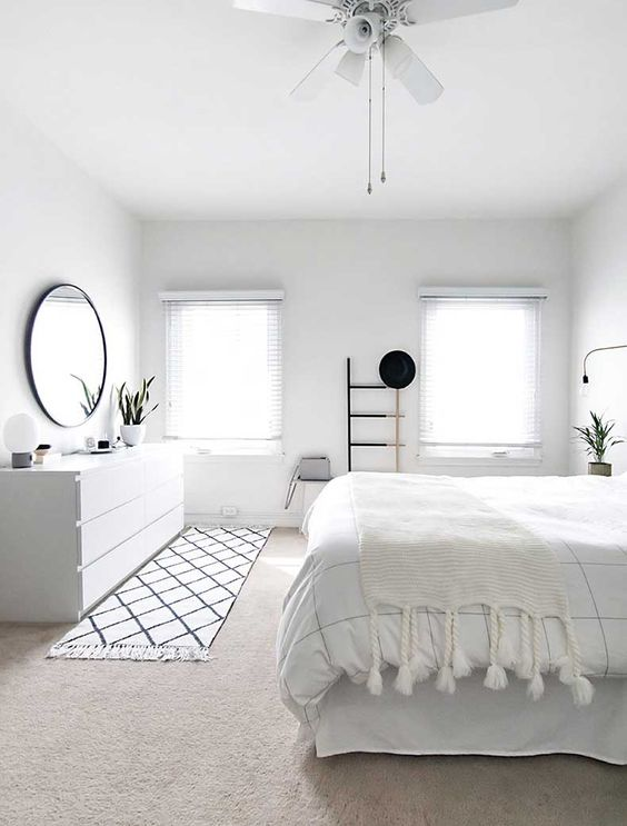 an airy Scandinavian bedroom with lot sof white, striped and tassel textiles, a black frame mirror, a sideboard