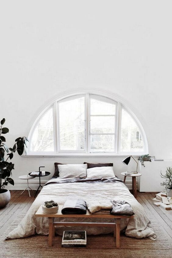 an airy white Nordic bedroom with an arched window, a bed, some wooden furniture and potted greenery