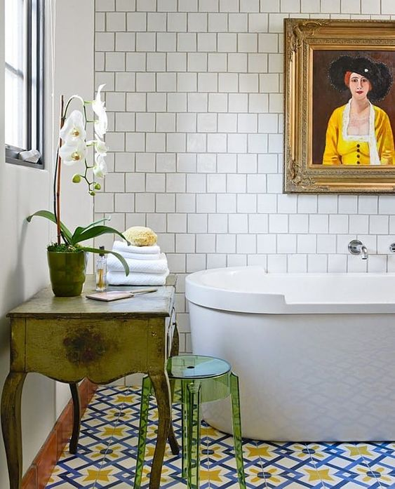 an eclectic bathroom with a colorful tile floor, a vintage vanity and an acrylic stool plus a white orchid for a refined touch