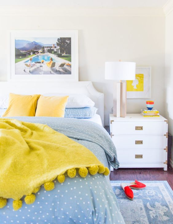 bright blue and sunny yellow bedding for a contrast and bold artworks make the space spring-summer-infused