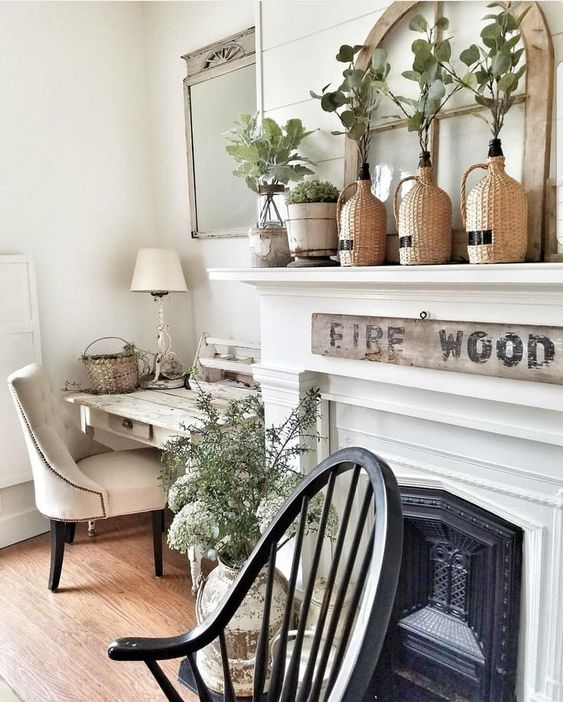 chic farmhouse spring mantel decor with greenery in bottles, potted greenery and more branches in vases