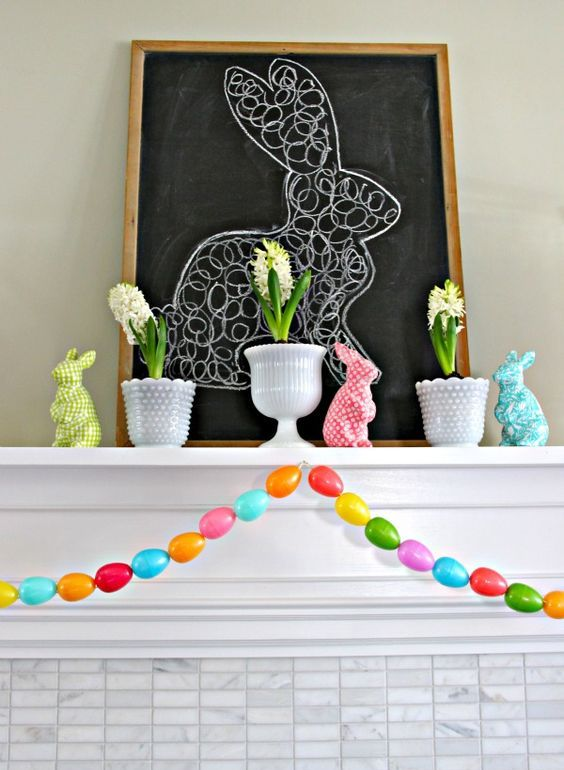 colorful easter mantel styling with a colorful egg garland, colorful bunny figurines and spring bulbs in pots