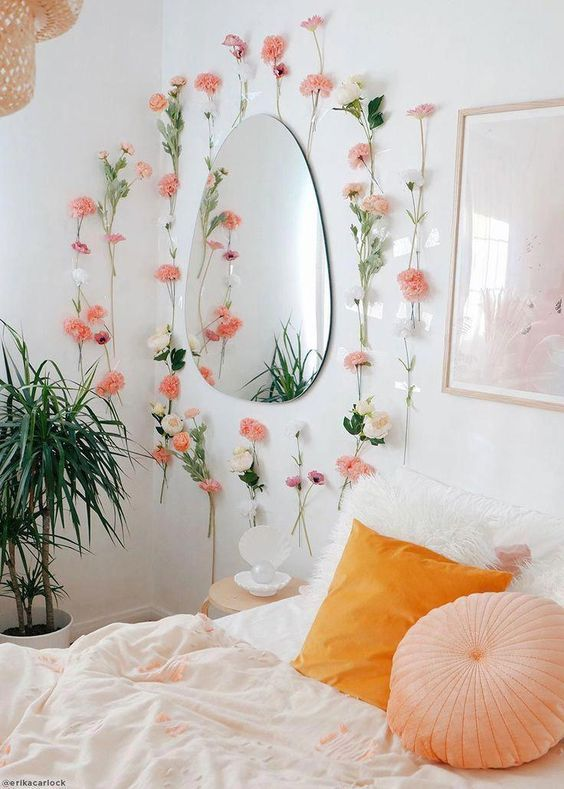 faux pink blooms attached to the wall and a marigold and peachy pillow make the bedroom spring-like