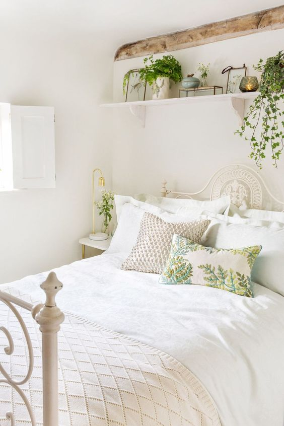 fresh greenery in pots and botanical pillows make the neutral space feel like spring and make it inviting