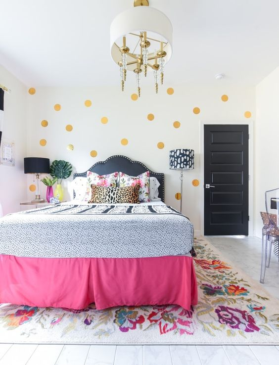 gold polka dots, a pink bed cover, some floral bedding make the space feel very spring-like