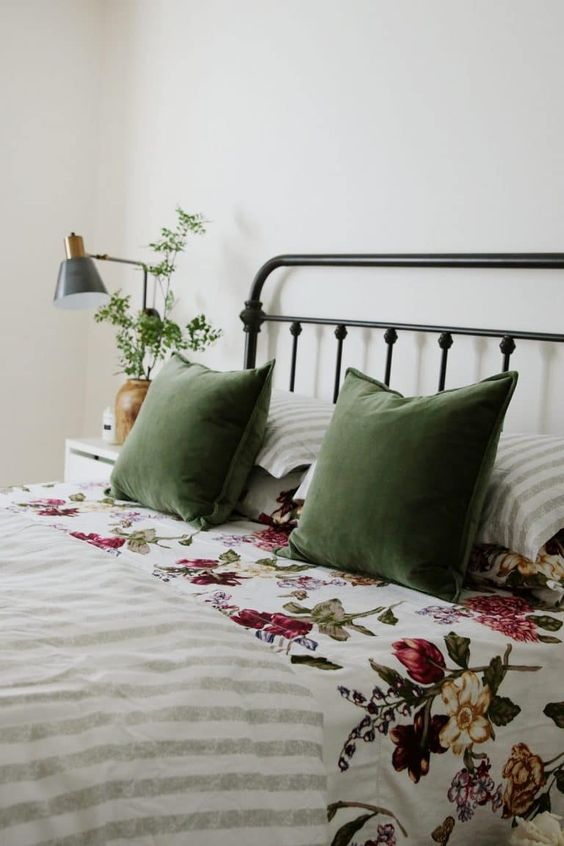 greenery in a vase, green pillows and floral bedding make the bedroom feel like spring or summer