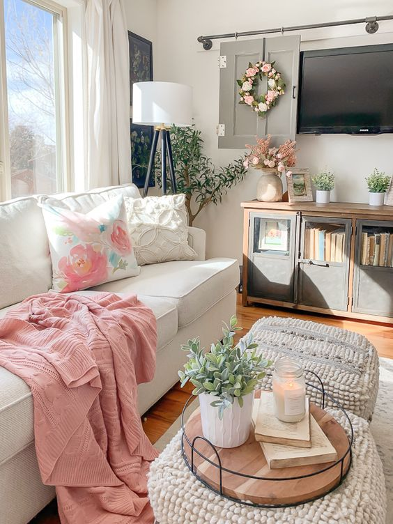 pink and floral textiles, potted greenery and faux blooms and candles make the neutral living room more chic