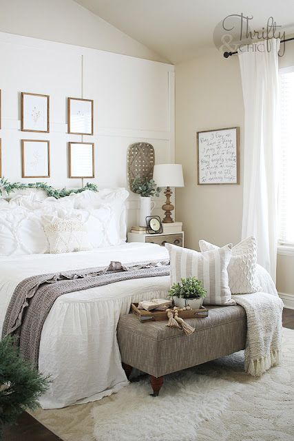potted greenery and a faux greeneyr garland make this neutral farmhouse bedroom refreshed and spring-like