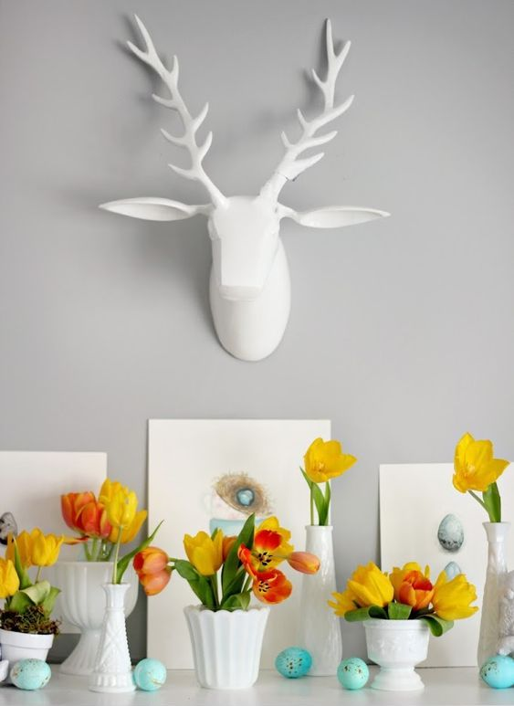 some faux speckled eggs, bright yellow tulip arrangements and egg artworks for an Easter mantel