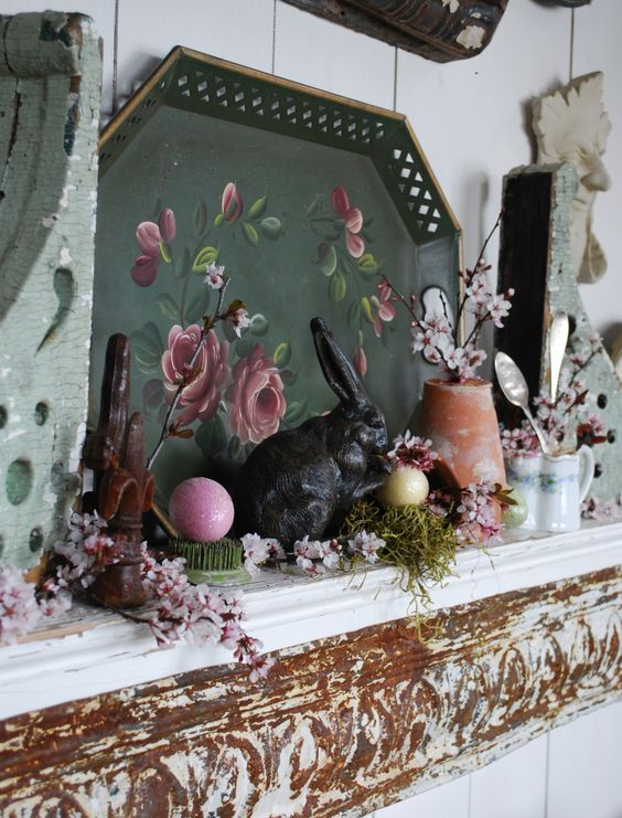 vintage spring mantel decor with a tray with art, some faux blooms and greenery, fake eggs and tableware
