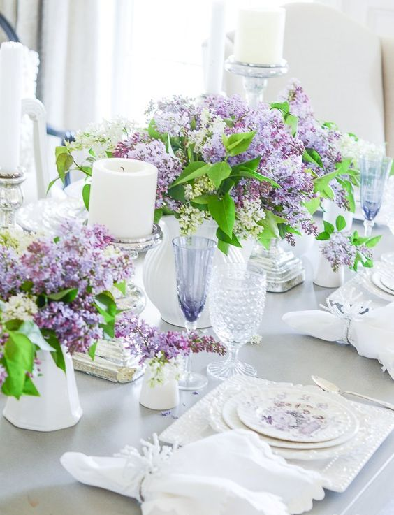 welcome spring with lush lilac centerpieces, candles, floral plates, white napkins and neutral cutlery