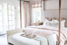 a beautiful feminine bedroom with a wallpaper accent wall, a canopy bed, blush bedding and curtains and a chic chandelier