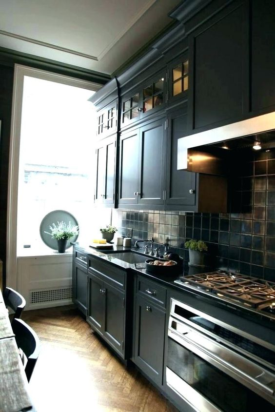 a black kitchen island with vintage cabinets, tiles, lights for a stylish masculine feel in the kitchen