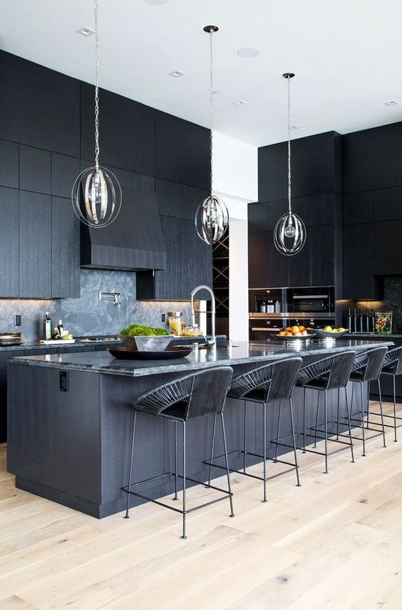 a black kitchen with textural cabinets, a kitchen island with a stone countertop and woven stools plus pendant lamps