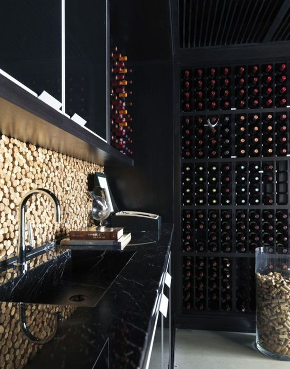 a black marble kitchen with a cork backsplash, a large wine cellar for a stylish moody masculine kitchen
