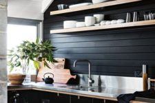 a black masculine kitchen with contrasting light-colored shelves, handles and countertops plus a burlap pendant lamp