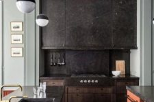 a black stone kitchen with a backsplash, a colorful kitchen island with a stone countertop and pendant lamps
