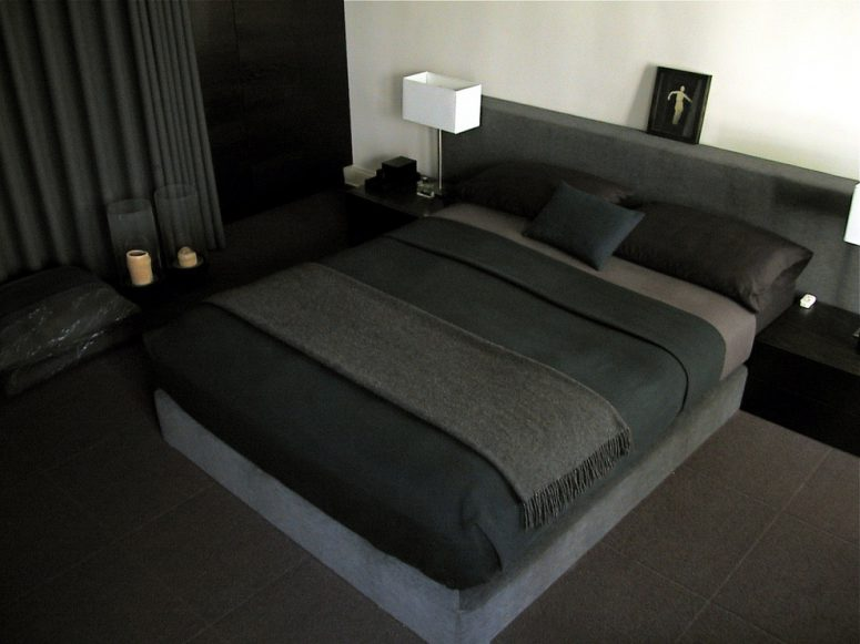 a boxspring upholstered in a gray pollack mohair velvet and a wall mount headboard in