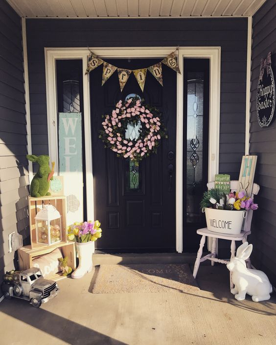 a bright spring Easter porch with a pink tulip wreath, a bunting, bunnies of moss and wood, tulips in buckets