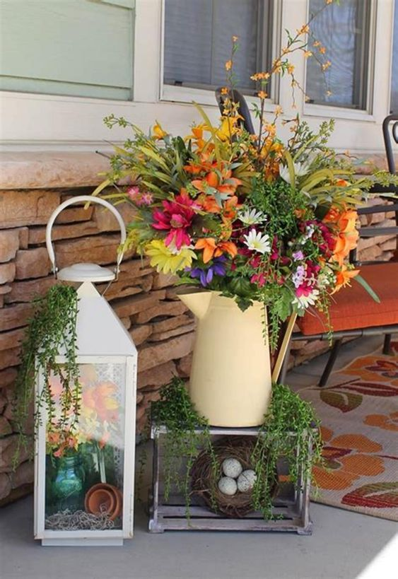 a bright decoration of a bold floral arrangement, a lantern with flowers, a faux nest with eggs and greenery
