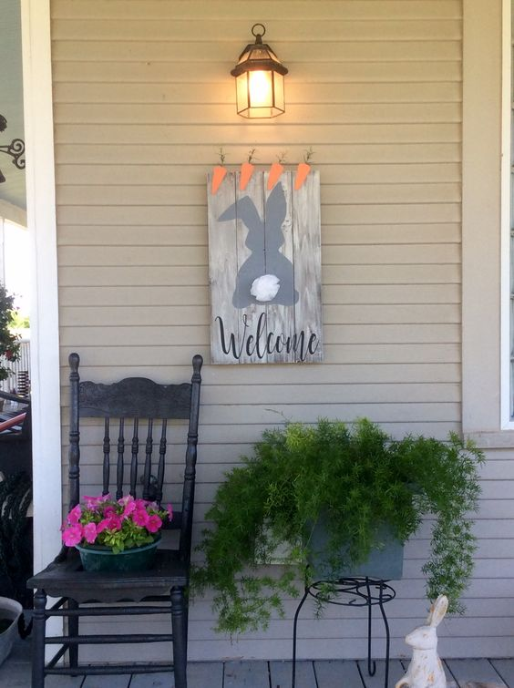 a bunny and carrot sign, potted cascading greenery and potted blooms and a faux bunny for porch decor
