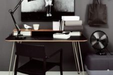 a catchy home office with cocnrete walls, a black deks with hairpinlegs, a black chair and catchy decor