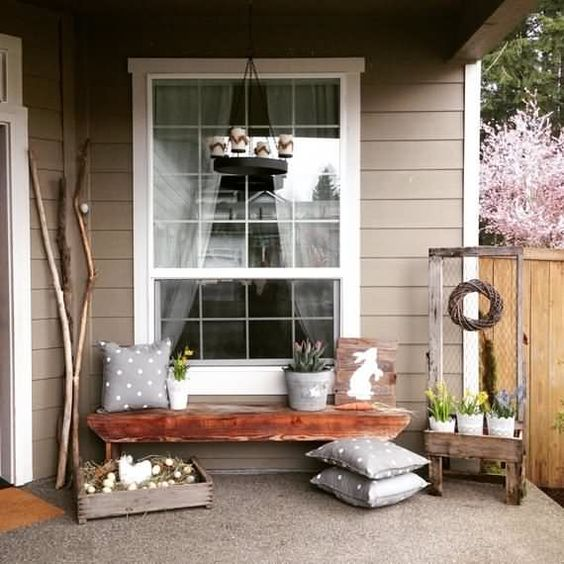 a chic Easter porch with polka dot pillows, a bunny sign, potted blooms and a crate with eggs and a fake hen