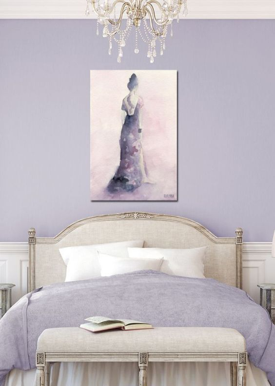 a chic feminine bedroom in lilac and neitrals, with lilac walls, neutral refined furniture, lilac bedding and an artwork plus a crystal chandelier