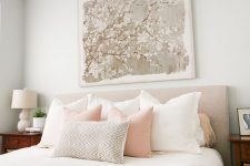 a chic feminine bedroom with grey walls, an upholstered bed, neutral and pastel bedding, wooden nightstands and a floral artwork