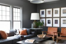 a chic masculine living room with dark furniture and walls, amber leather touches and chairs, some cushions and a coffee table