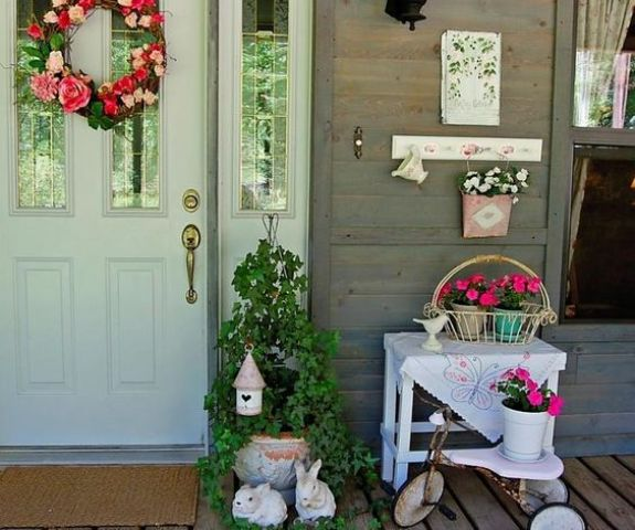a colorful Easter porch with a bright bloom wreath, potted flowers, bunnies and a little bird house