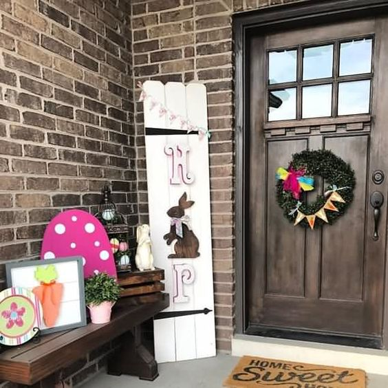 a colorful Easter porch with some themed artworks, a greneery wreath and a HOP and bunny sign