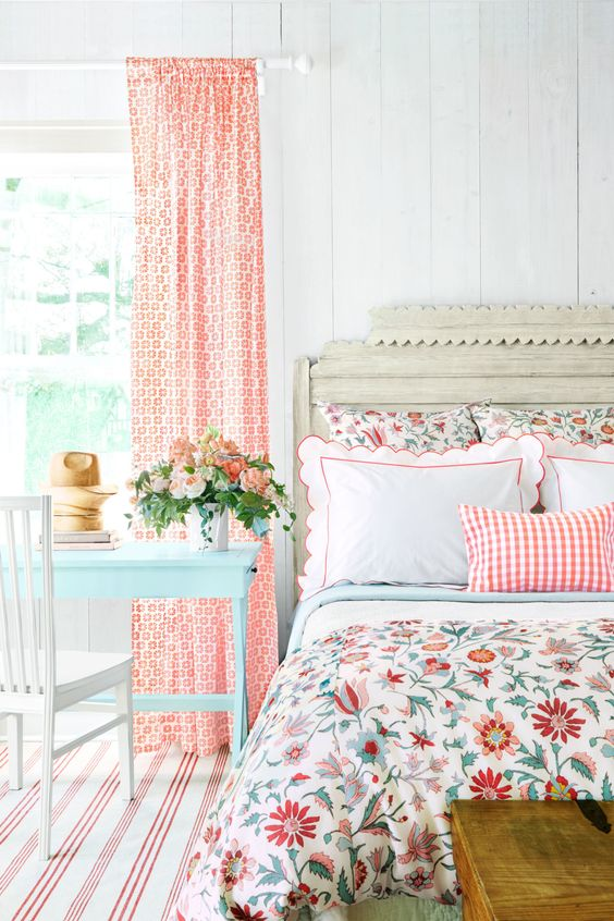 a colorful vintage bedroom with elegant vintage furniture, floral bedding, printed curtains, a blue table and bold blooms