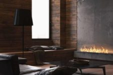a contemporary living room with a fireplace, dark leather furniture, a stylish chandelier and a large window plus lamps
