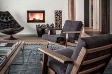 a contemporary living room with dark furniture, a built-in fireplace and firewood storage, a dark rug and a coffee table