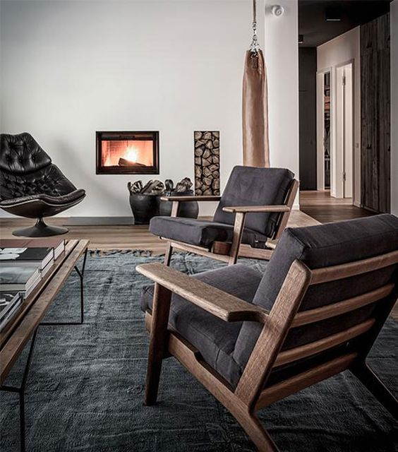 a contemporary living room with dark furniture, a built in fireplace and firewood storage, a dark rug and a coffee table