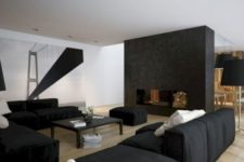 a contemporary masculine living room with a fireplace, black furniture, a large artwork and a black coffee table