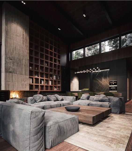 a contemporary masculine living room with dark walls, a large storage unit, a fireplace, grey sofas and a wooden table