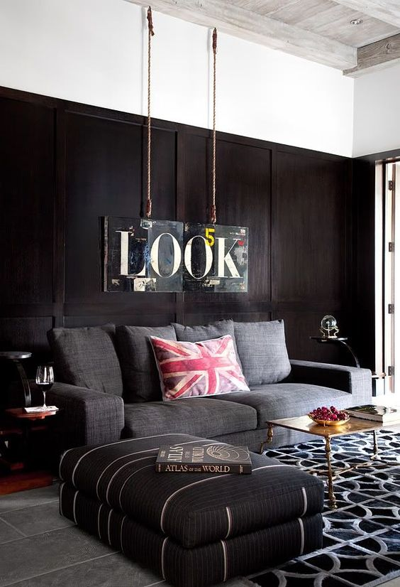 a contemporary masculine living room with dark walls, upholstered furniture, a printed rug, a metal table and a sign